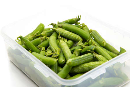 Garden peas in pods freshly picked in a plastic container,  isolated on a white background.  Grow your own concept 写真素材