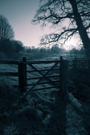 Wooden gate in a field meadow on a farm.  With colour toning 写真素材
