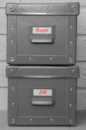 Storage boxes with receipts and bills written on labels in red.  With a grey brick background