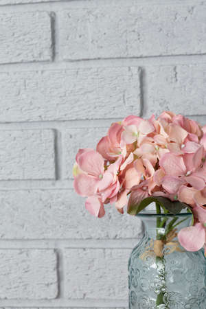 Artificial pink bunch of Hydrangea flowers in a glass vase.  Grey brick background Stock Photo