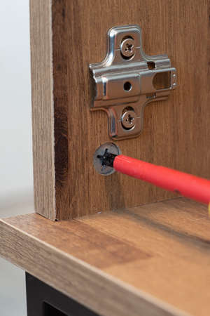Flat pack wooden cabinet being assembled with a screwdriver.  Self assembly furniture concept Stock Photo