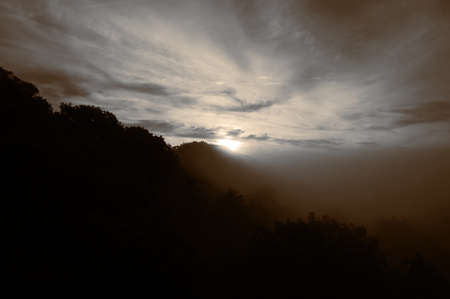 Sun rising over woodland hill on a misty morning.  With colour toning Stock Photo