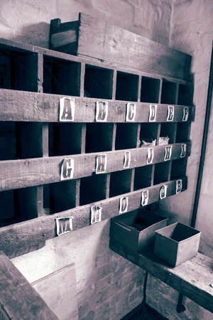Pigeon hole box shelving on a wall in an old vintage workshop. With colour toning Stock Photo