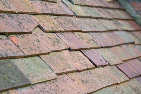 Old traditional weathered clay roof tiles.  With shallow depth of field