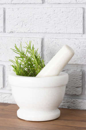 Rosemary in a white granite pestle and mortar.  Wooden worktop counter with grey brick background Stock Photo