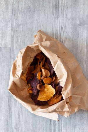 Vegetable crisps in a paper bag. Sweet potato, beetroot and parsnip flavour. Vegan food concept