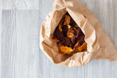 Vegetable crisps in a paper bag.  Sweet potato, beetroot and parsnip flavour.  Vegan food concept