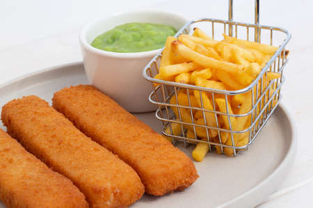 Fish fingers served with chips in a wire basket and mushy peas.  White wood background