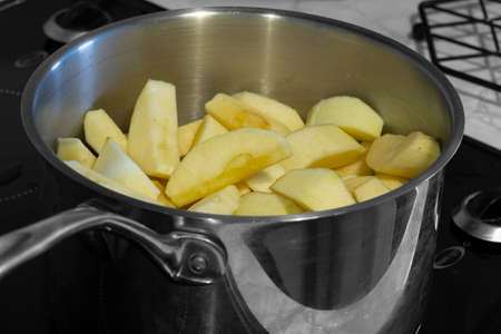 Apples stewing in a saucepan on a hob stove.  Selective colour Stock Photo