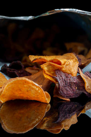 Bag of vegetable crisps reflected on a black background.  Sweet potato, beetroot and parsnip flavour.  Vegan food concept Stock Photo