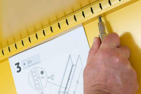 Man assembling a yellow metal cabinet with a screwdriver and instructions.  Self assembly flat pack furniture concept Stock Photo