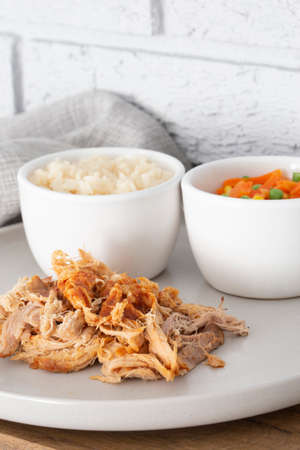 Pulled pork with rice and vegetables on a grey plate.  Grey brick background with a tea towel Stock Photo