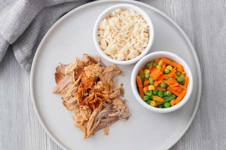 Pulled pork with rice and vegetables on a grey plate.  Grey wood background with a tea towel