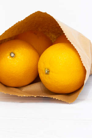 Oranges in a brown paper bag on a white wood background.  Environmentally friendly packaging concept