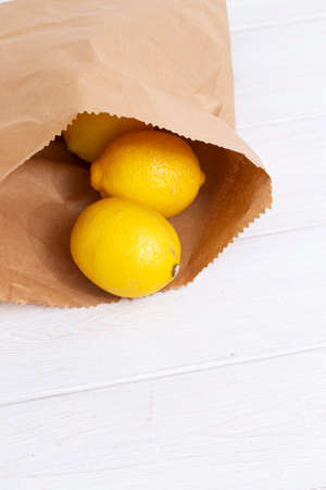 Lemons in a brown paper bag on a white wood background.  Environmentally friendly packaging concept