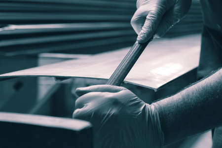 Man filing deburring a metal panel with a file.  With colout toning Stock Photo