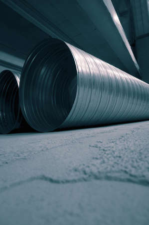 Galvanised steel ducting tubing for air extraction on the floor of a factory warehouse.  With colour toning
