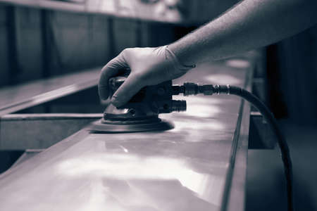 Man using orbital sander to prepare a metal panel.   With colour toning