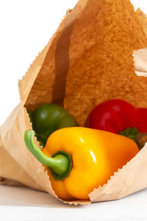 Yellow, red and green peppers in a brown paper bag on a white wood background.  Environmentally friendly packaging concept Stock Photo