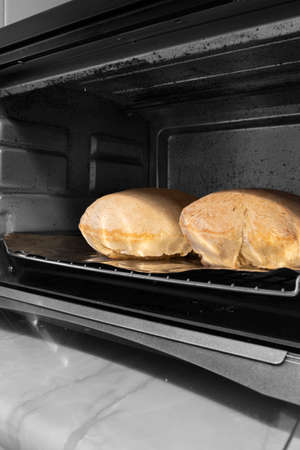 Loaves of bread cooked in an electric oven.  Selective colour image