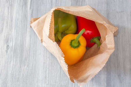 Yellow, red and green peppers in a brown paper bag on a grey wood background.  Environmentally friendly packaging concept
