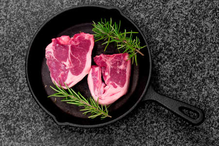 Lamb loin chops with rosemary in a cast iron frying pan.  On a black granite background