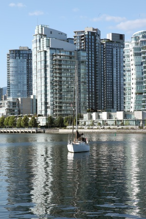 close quarters: A sailboat & modern skyscrapers in Vancouver BC Canada. Stock Photo