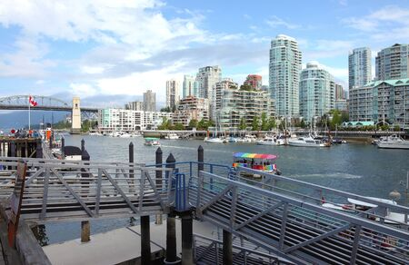 A ferry terminal in Granville island in Vancouver BC., Canada overlooking the skyline across False creek. photo