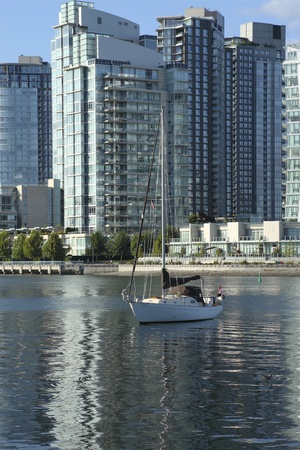 close quarters: A sailboat   modern skyscrapers in Vancouver BC Canada  Stock Photo
