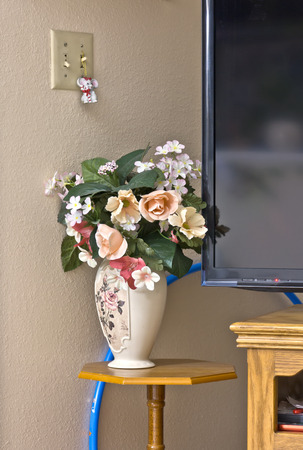 Still Life Plastic Flowers Vase Stand And Tv Corner Stock Photo