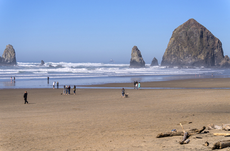 Canon Beach Oregon walks on the shore on a warm day.