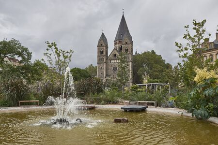 Metz France Cathedral park and fountain with overcast skies.