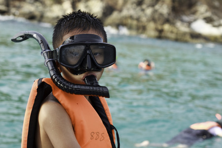funny ox: MAY 11 2014   SAMET ISLAND THAILAND.Summer vacation - Portrait of happy boy in face masks and snorkels, sea in background. Editorial