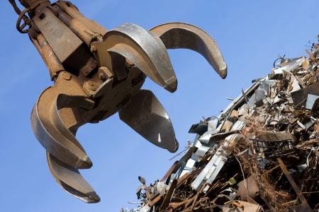 grúa de grabber en la pila de metal oxidado