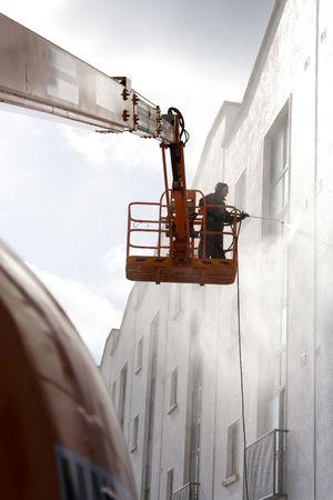 woker in platform wash a building Imagens