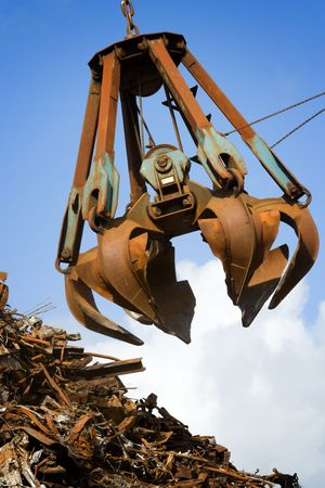 scrap heap: crane grabber loading a metal garbage