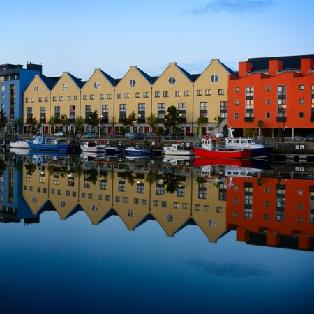 morning vew on row of buildings and fishing boats at Galway Dock reflected in the water