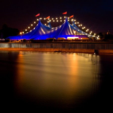 Sircus tent with lights on the bank of river, Galway