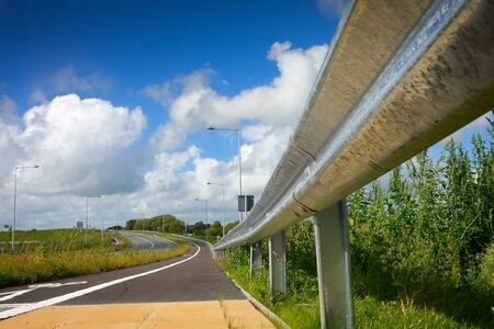 hiway: road with protective metal side fence and blue sky with clouds Stock Photo