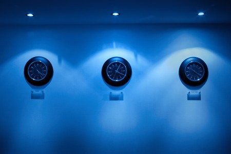 row of clock on the wall illuminated by lamps Stock Photo - 7976937