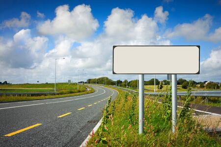 curve road: road with sign pole and blue sky with clouds Stock Photo