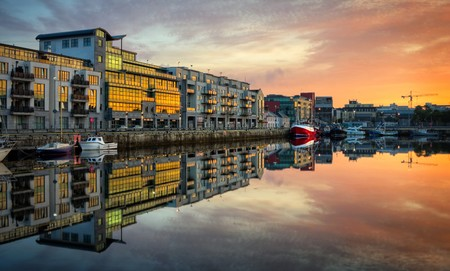 morning view on row of buildings and fishing boats in Galway Dock with sky reflected in the water, HDR image