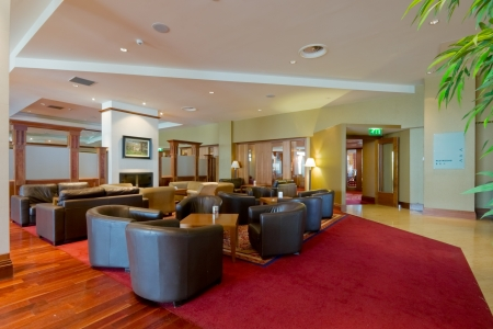 hall with leather arm-chairs and red carpet in modern Hotel interior photo