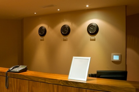 hotel reception desk with phone and row of clock on the wall Stock Photo