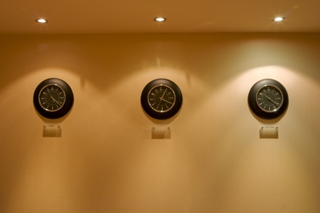 row of clock on hte wall illuminated by lamps Stock Photo - 8363452