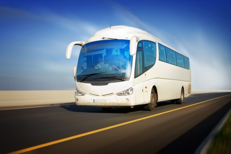 transportation travel: white touristic bus in motion on the highway and blurred background