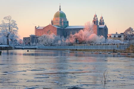 Galway Cathedral in First sunlights and Corrib river covered by ice at cold winter morning Stock Photo