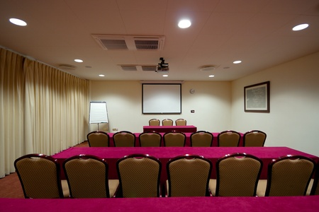 Conference room Interior with tables raw of chairs, screen and projector photo