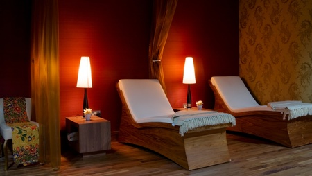 SPA restroom interior and row of wooden beds with white towels