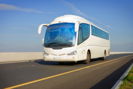 white touristic bus on the highway and blue sky photo
